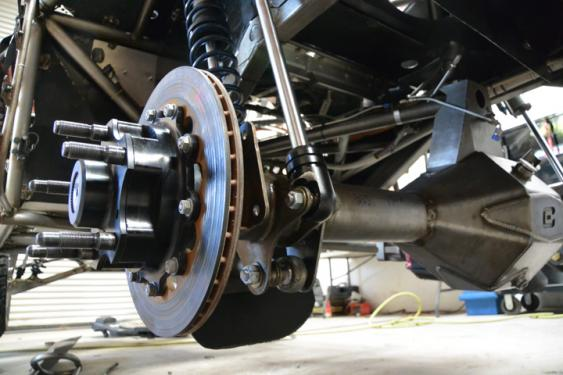 A full-floating hub on the end of a Currie 9-Inch axle provides maximum strength for racing. The guard in front of the lower shock ends protects them from anything that gets spit up off the course.